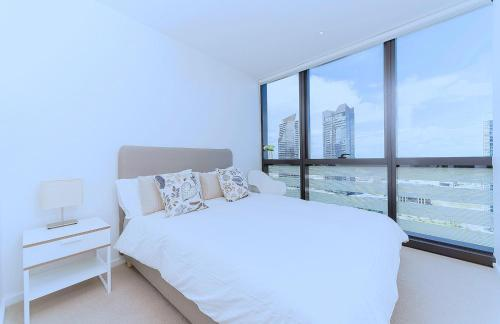 A bed or beds in a room at Brilliant Victoria Harbour Waterfront