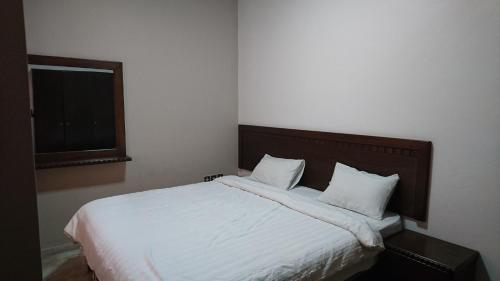 A bed or beds in a room at Noor Hotel Apartments
