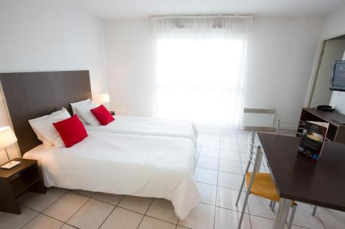 A bed or beds in a room at All Suites Bordeaux Mérignac - Aéroport