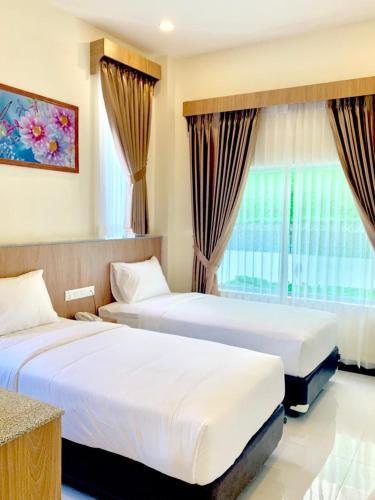 A bed or beds in a room at Bintan Lumba Lumba Inn Hotel