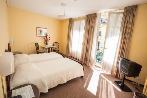 Ein Bett oder Betten in einem Zimmer der Unterkunft Hôtel Résidence Cité-Verdaine