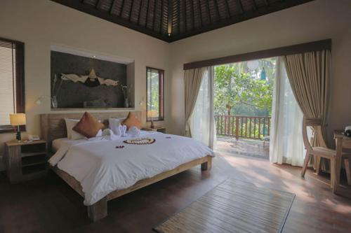 A bed or beds in a room at Harum Sari Ubud Private Villa