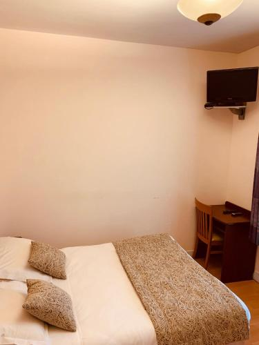 A bed or beds in a room at Le Val D'or