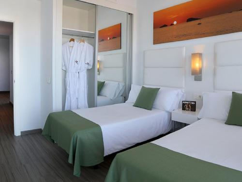 A bed or beds in a room at AxelBeach Ibiza Suites Apartments Spa and Beach Club - Adults Only
