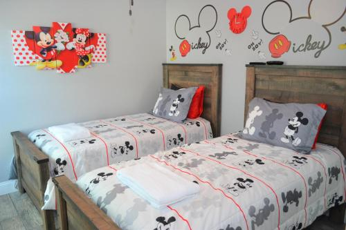 A bed or beds in a room at Mickey's Landing - Luxury 5 Star Family 4 Bedroom with Pool, Hot Tub, Games Room & BBQ,5 Mins Disney
