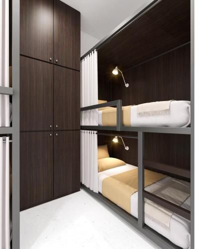 A bunk bed or bunk beds in a room at Bond Boutique Capsule Hotel @ Bugis
