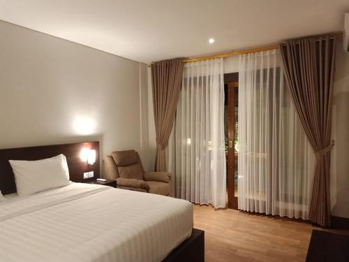 A bed or beds in a room at The Surya Kuta Villa