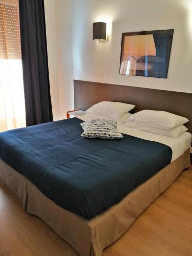 Un ou plusieurs lits dans un hébergement de l'établissement Hôtel Colbert