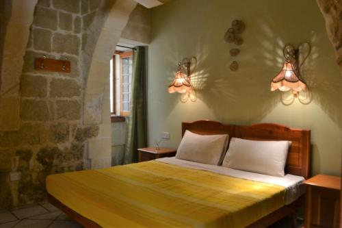 A bed or beds in a room at Ta' Gilja Farmhouse