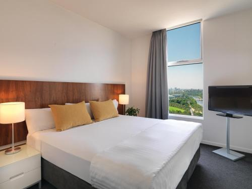 A bed or beds in a room at Adina Apartment Hotel Melbourne Flinders Street