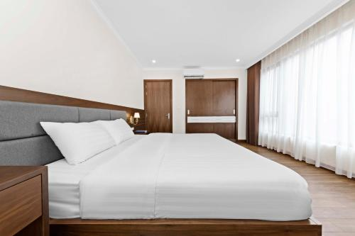 A bed or beds in a room at Newsky Serviced Apartment
