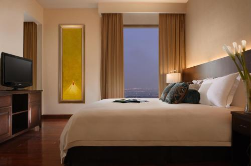 A bed or beds in a room at Fraser Suites Hanoi
