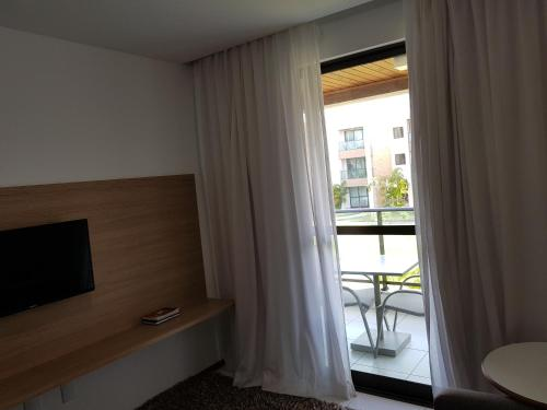 A television and/or entertainment centre at Residence Resort - Barra de São Miguel