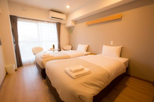 A bed or beds in a room at アルセ琉球ハーバーステイ
