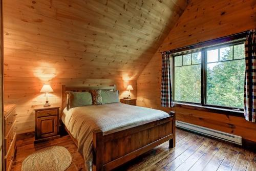 A bed or beds in a room at Le Village Windigo