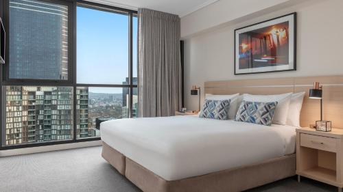 A bed or beds in a room at Oaks Brisbane on Charlotte Suites