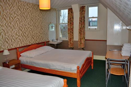 A bed or beds in a room at London Visitors Hotel