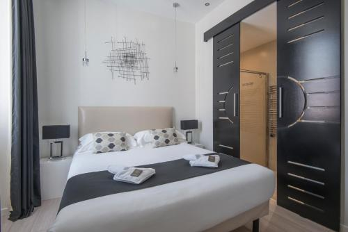 A bed or beds in a room at O Carré Croisette Cannes