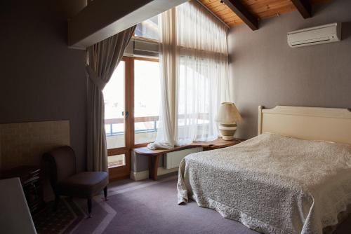 A bed or beds in a room at Dom Solntsa in Krasnaya Polyana Apartments