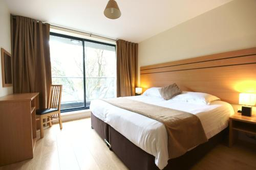 A bed or beds in a room at Lodge Drive Serviced Apartments