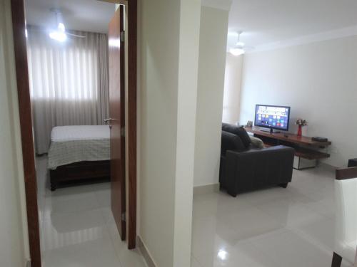 A television and/or entertainment centre at Apartamento Completo na melhor localização da Praia do Morro, possui 3qts sendo a suite com Ar Condicionado, 2 vagas de garagem gratuitas, internet - Varandão Sol da Manhã, prédio e apt novos