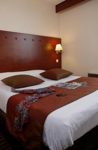 A bed or beds in a room at Hôtel Gallieni