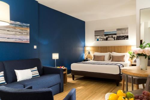 A bed or beds in a room at Citadines Apart'hotel Cannes Croisette
