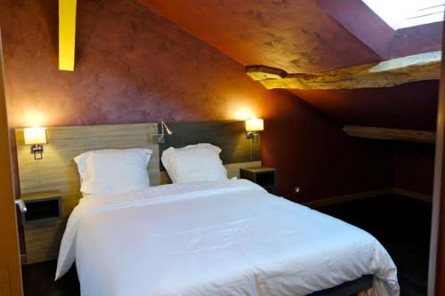 A bed or beds in a room at Couleurs du Daumail