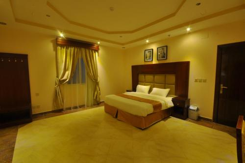 A bed or beds in a room at Hadeiat Kindah Hotel Suites