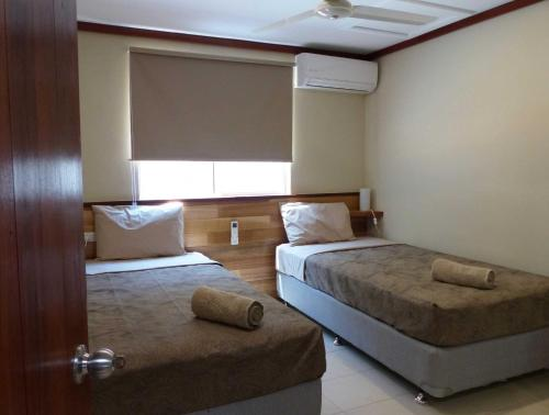 A bed or beds in a room at The Cocos Padang Lodge