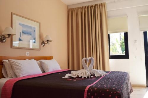A bed or beds in a room at Anna Hotel Apartments