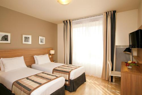 Un ou plusieurs lits dans un hébergement de l'établissement Séjours & Affaires Paris-Vitry