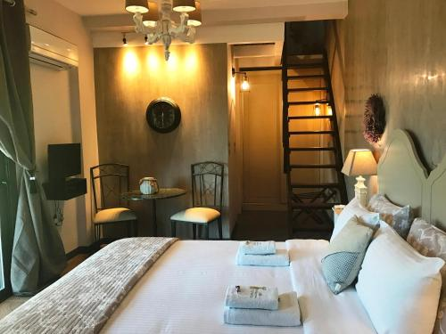 A bed or beds in a room at Villa Vravrona Tower & Suites