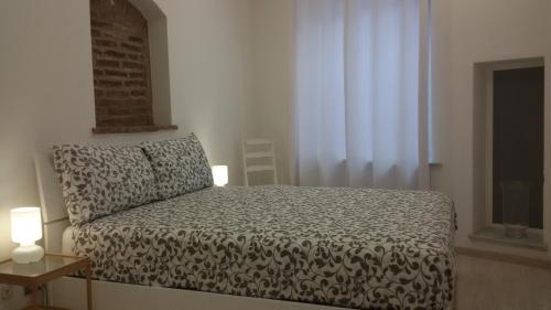 A bed or beds in a room at Piazzetta dei Consoli Apartment