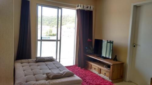 Una televisión o centro de entretenimiento en Apartamento Cachoeira do Bom Jesus