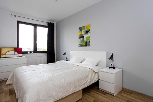 A bed or beds in a room at Wola Apartment