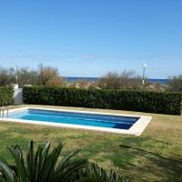 primera línea de la playa de oliva con jardín y piscina.