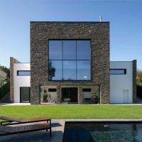 Casa moderna con piscina y vistas al bosque.